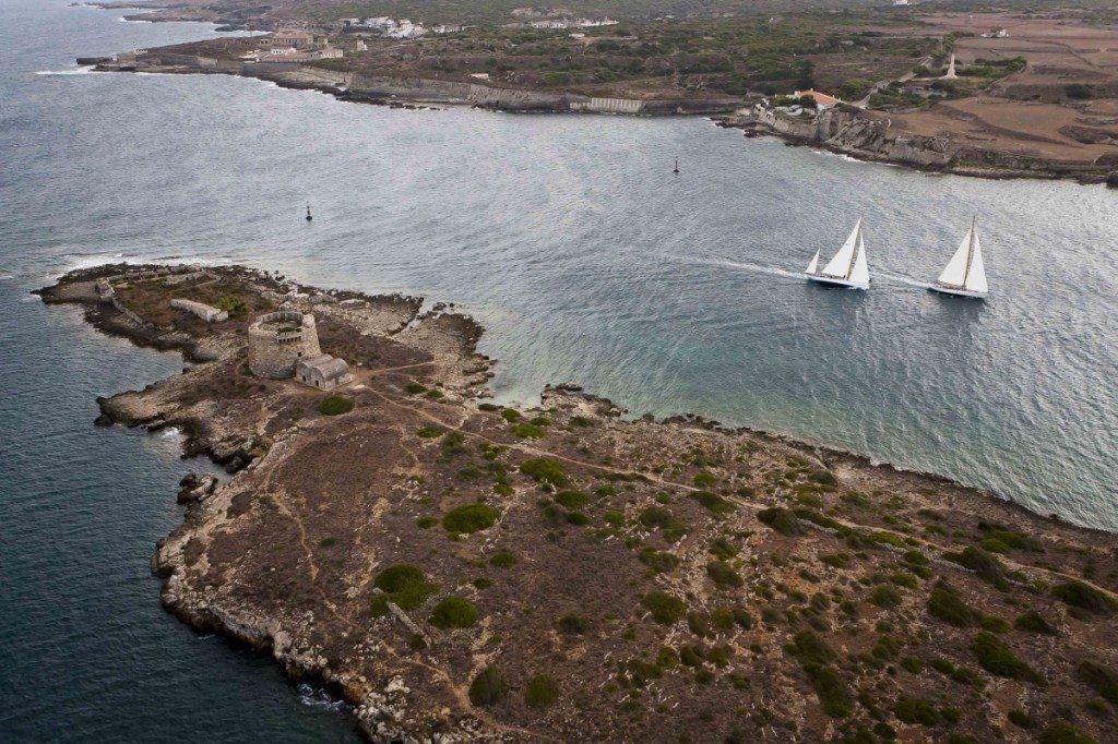 Fotografía de la IX Copa del Rey de Barcos de Epoca. Los barcos navegan en frente del Fuerte de San Felipet, en la entrada del Puerto de Mahón.