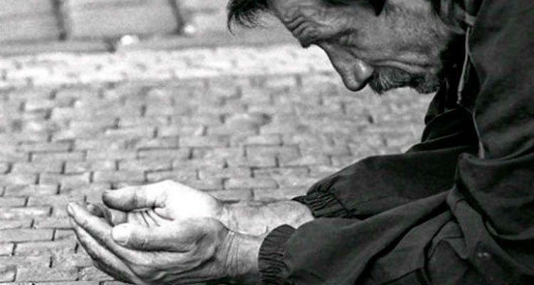 Representación fotográfica de un mendigo sentado en la acera de una calle pidiendo dinero.