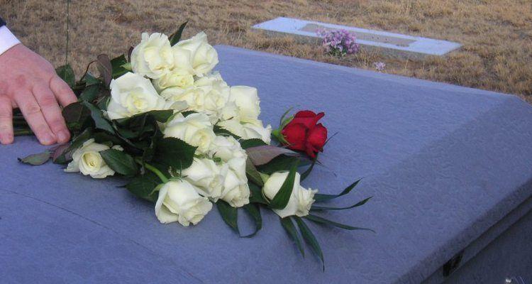 Señor dejando flores sobre el ataúd durante el entierro.